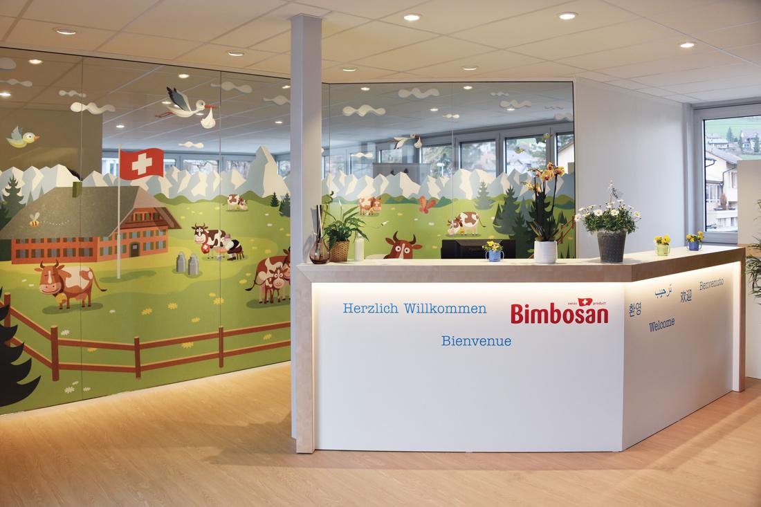 Showroom Empfang mit grossem Bild auf foliertem Glas: Schweizer Bauernhaus, Kuhweide und Bergpanorama in kindlich froehlichem Bauernmalereistil