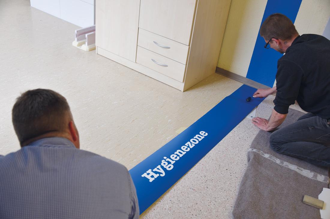 Blaue Signalisation fuer die Hygienezone wird als Streifen ueber die Wand und den Boden gezogen