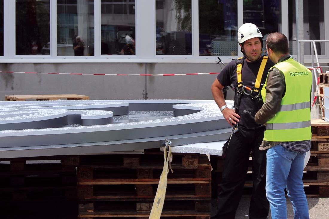 Zusammenbau der Leuchtlogo-Installation auf dem Boden in der Anlage der GE. Gesamtgewicht: 980 kg