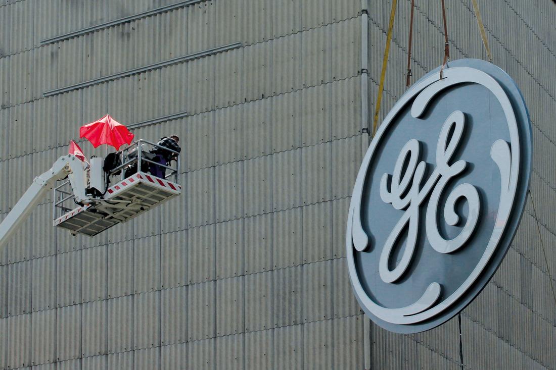 Frontwork-Spezialisten auf dem Skyworker bei der Montage des Leuchtlogos. Das Logo haengt noch in der Luft vor der Fassade.