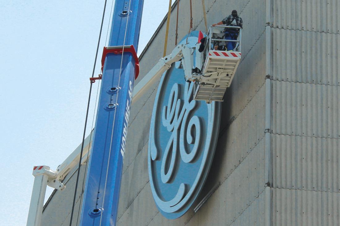 Frontwork-Spezialisten auf dem Skyworker bei der Montage des Leuchtlogos: Nahaufnahme der Platzierung der Installation an der Fassade.