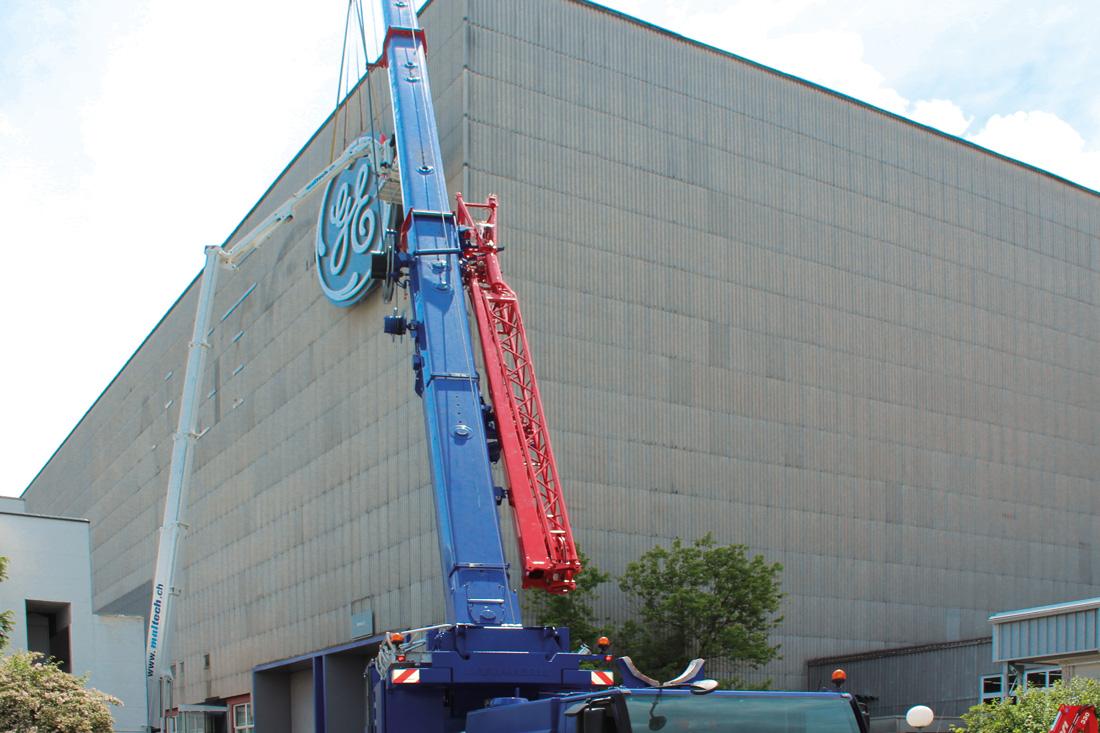 Frontwork-Spezialisten auf dem Skyworker bei der Montage des Leuchtlogos: Aufnahme vom Boden der Platzierung der Installation an der Fassade.