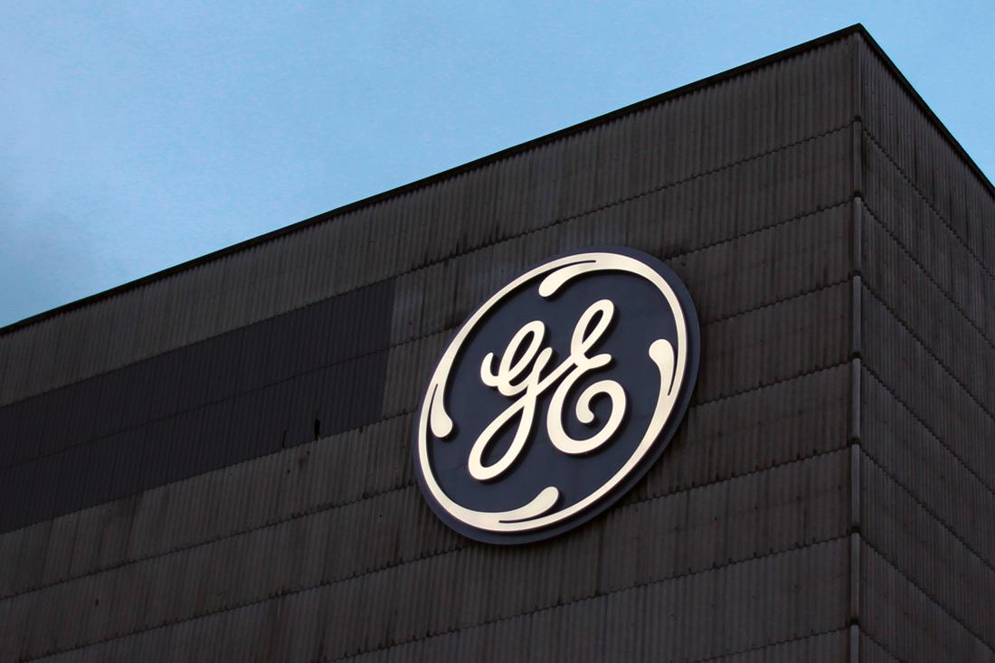 Leuchtlogo Fassade General Electric; mit gedimmtem Licht in der Daemmerung, auf der dunklen Well-Eternit-Fassade der General Electric.