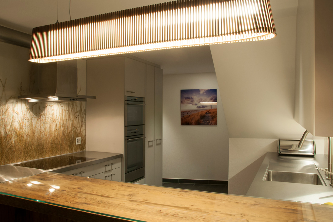 Kuechenrueckwand aus Konzeptglas mit eingeschweisstem Heu und Holztheke