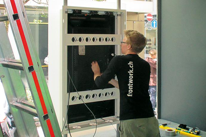 frontwork-Mitarbeiter montiert das digitale Schaufenster vor Ort