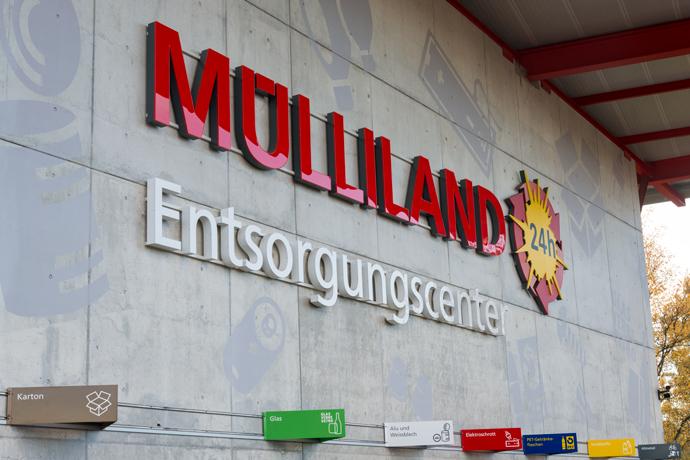 Rote Leuchtschrift an der Fassade Muelliland, Entsorgungscenter mit leuchtender Sonne mit natuerlichem Lichteffekt