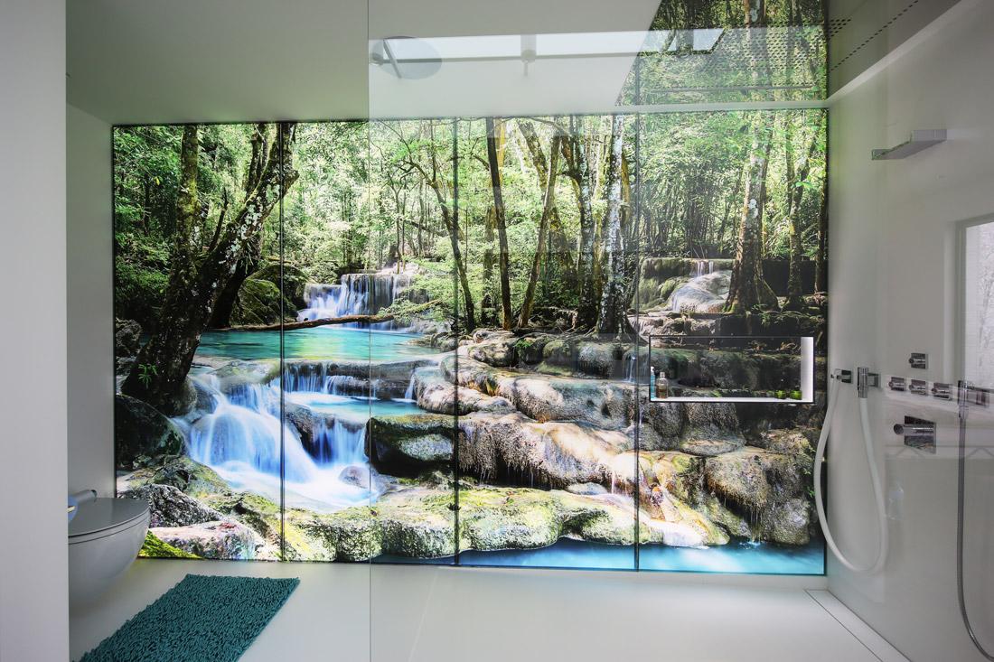 Glaswand hintergrundbeleuchtet, mit Regenwald-Sujet. Ein Bach fliesst in die Dusche