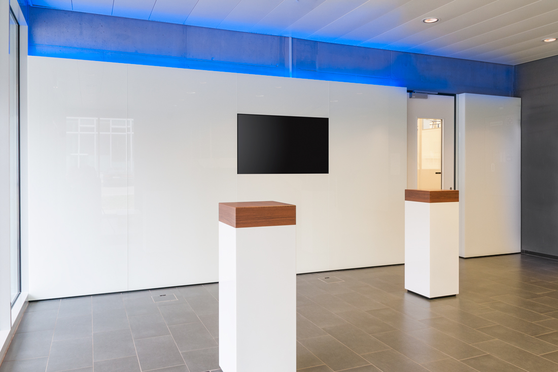 Repraesentativer Empfangsbereich mit bedruckter Glaswand und wechselnden Farb- LED's, leuchtet Blau