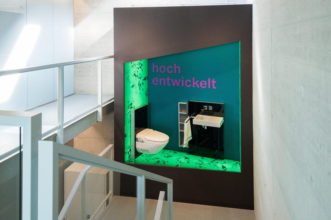 Beleuchtete Glaswand in einer Treppenhausnische: Hell leuchtendes Gruen mit Schriftzug: Hoch entwickelt