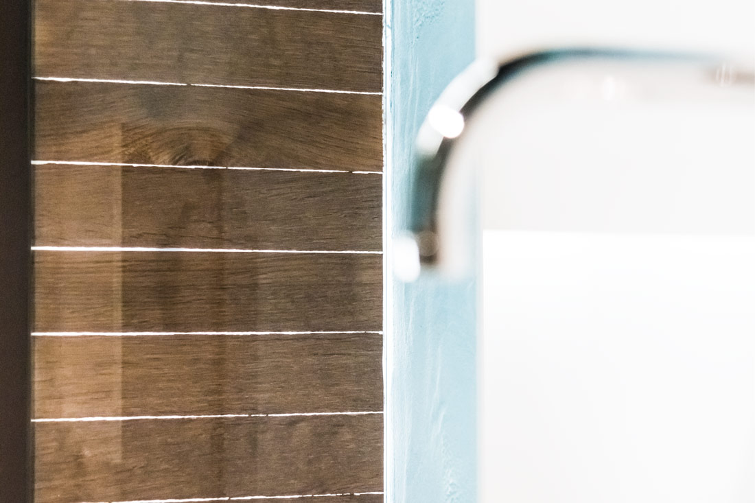 Glaswand mit eingearbeitem Holz als dekoratives und pflegeleichtes Element