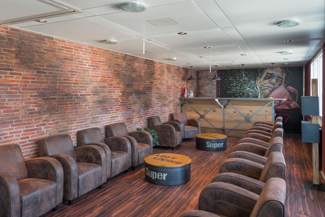 Raumgestaltung im Loft-Style: Lounge mit Ledersofas und Backsteinwand, Hingucker die Tische im Oelfass-Look mit Aufschrift: LOFT-LIVING