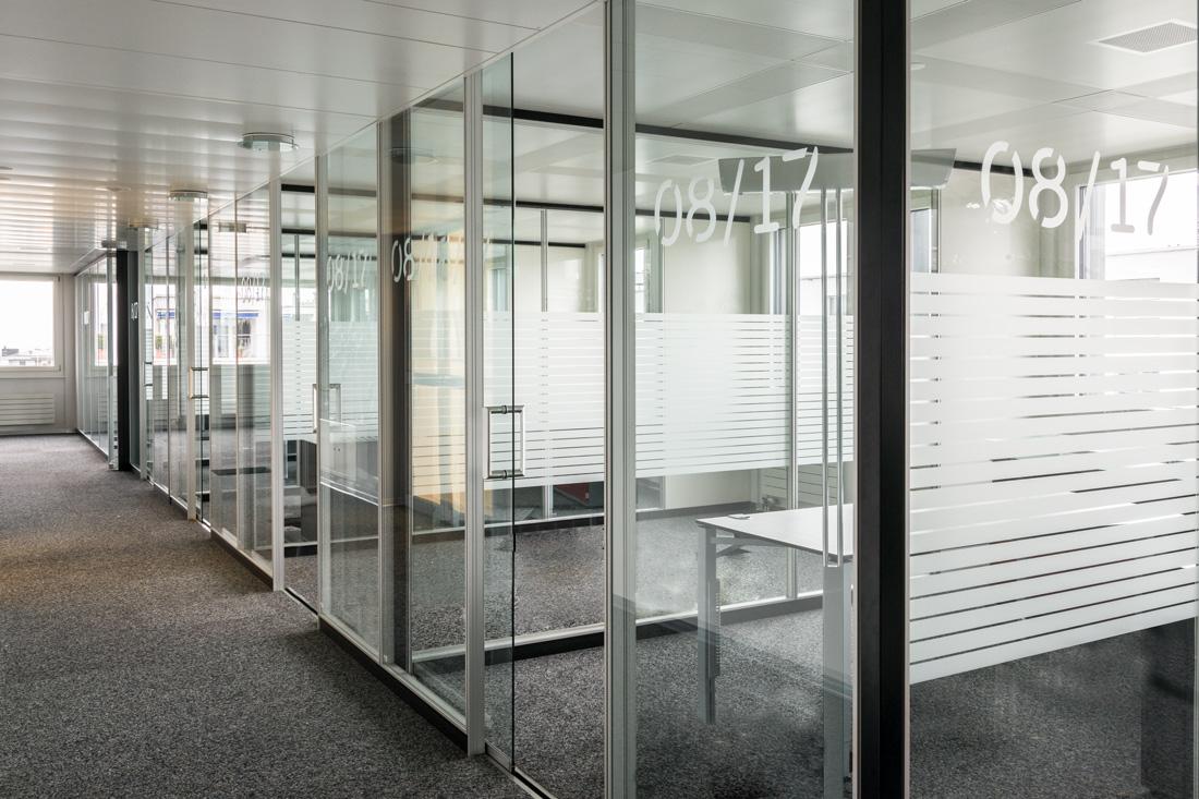 Reihe von Rauemen mit Glaswanden getrennt - hell durchlaessig und mit Kristallfolie angebrachter Sichtschutz