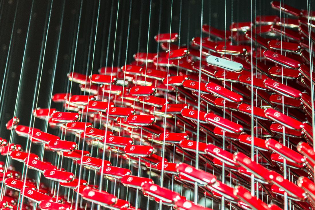 15'283 rote Sackmesser und ein weisses dazwischen symbolisiert die Schweiz im Globus
