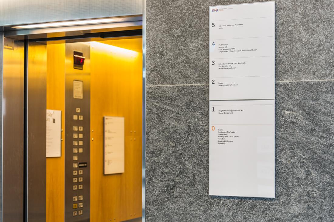Liftschild zur Wegleitung. Das Re-Branding von Beschriftungskonzept zieht sich durch, vom Eingang bis zur Toilette.