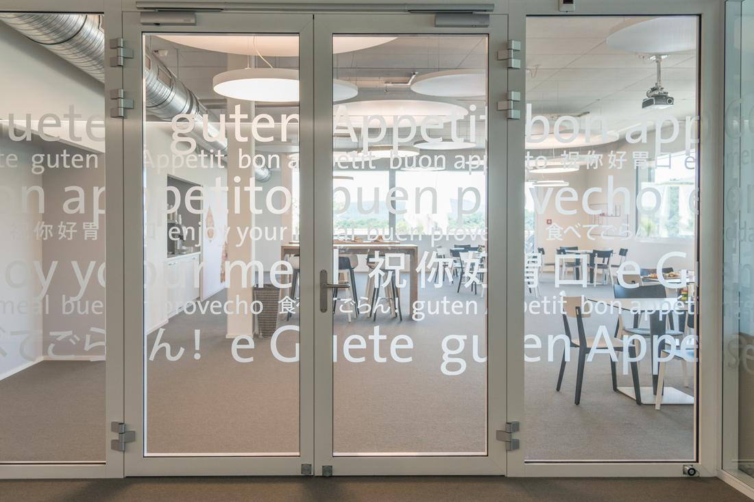 Office Branding der Cafeteria im Laeckerli Huus: Transparentfolien auf Glas mit Aufschriften: En Guete in verschiedenen Sprachen