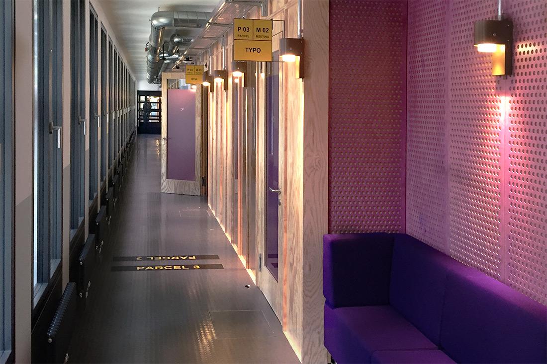 Buero der Zukunft: Stockwerke in verschiedenen Farben gestaltet. Gelbe Stechschilder weisen den Weg zu den Meetingraeumen.