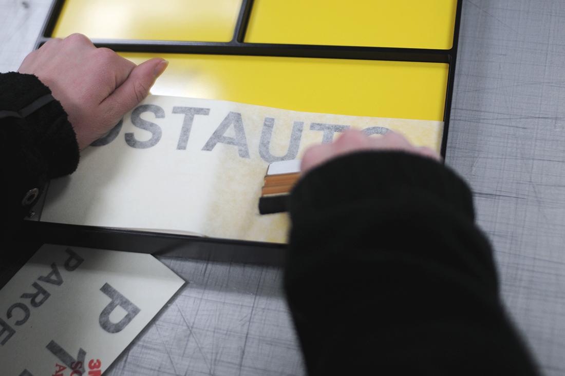Postgelbe Stechschilder werden beklebt mit einem Folienplott.
