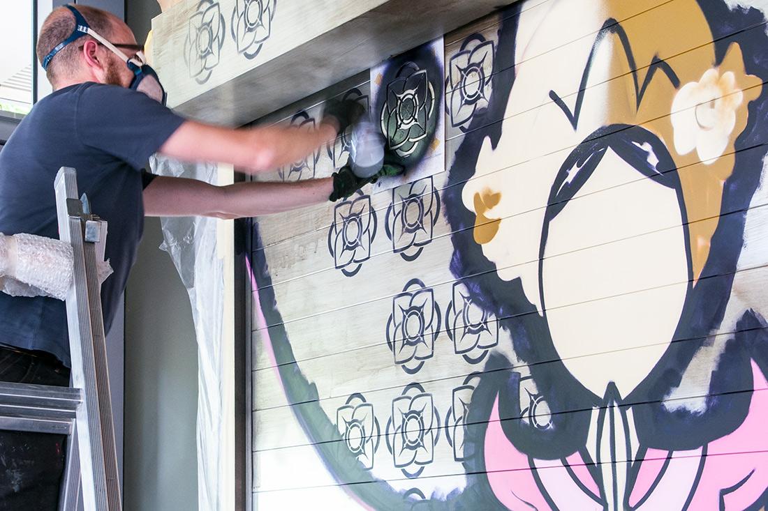Vintage-Umsetzung der Garagenrollwand: Lotusblumen werden mit Schablonen auf die Garagenrollwand aufgesprayt