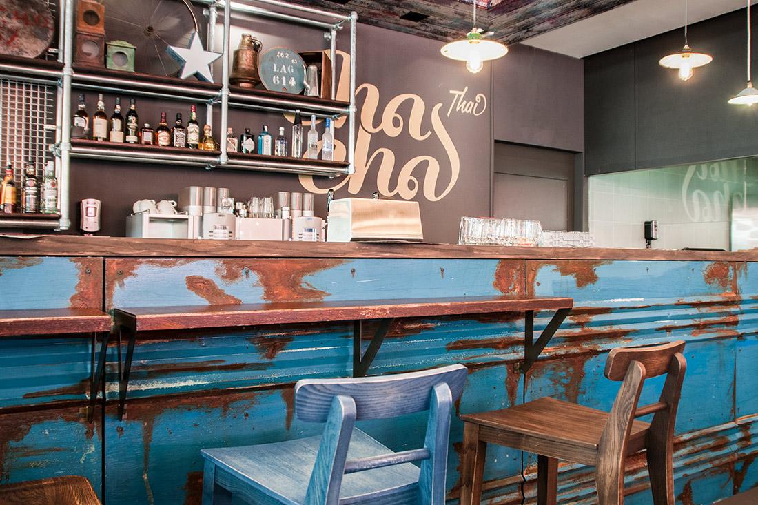Die Bar im Vintage-Look: Bunt gemischte Stuehle, verbeulte und verrostete Theke wirken authentisch und vernoestlich