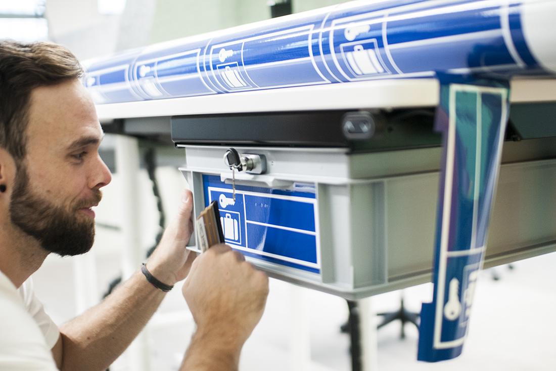 Mitarbeiter klebt Box im Look eines Schliessfachs
