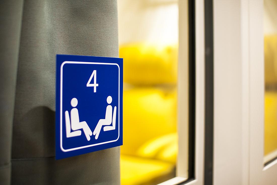 Beschriftung der Sitzungszimmer mit Piktogrammen, zwei sitzende Personen in Wagenabteil mit Nummer vier