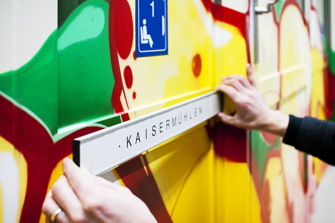 Umsetzung des Brand-Look mit austauschbaren Schildern; Beschriftung einer Wand mit dem Look eines Zug-Abteils