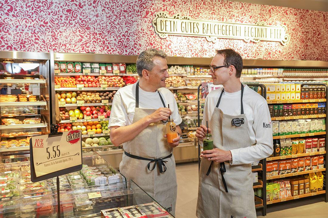 Ladengestaltung Karma-Verkauefer mit Schoss probieren einen Fruchtjus vor den farbenfrohen Regalen