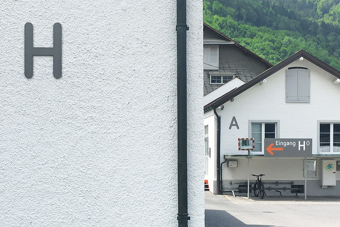 3D Buchstaben an der Fassade erleichtern die Orientierung. Stechschild mit wegweisendem Pfeil.