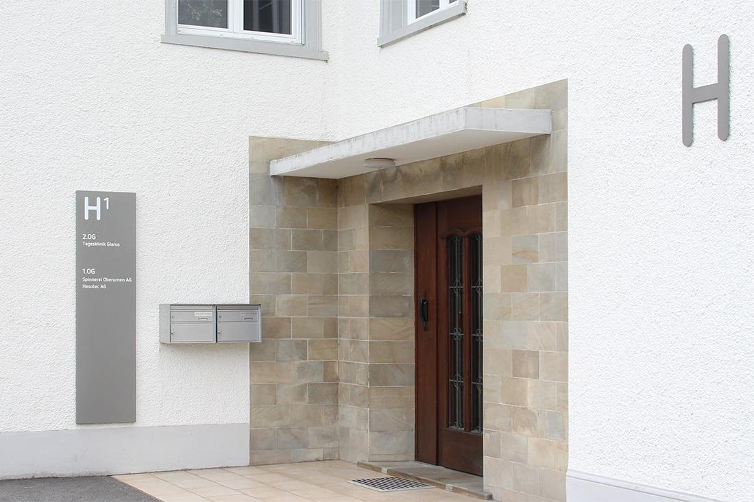 Orientierungsschild, welches als Wegweiser dient und mit einer verdeckten Montage an die Wand angebracht wurde. 3D Buchstaben an der Fassade erleichtern die Orientierung.
