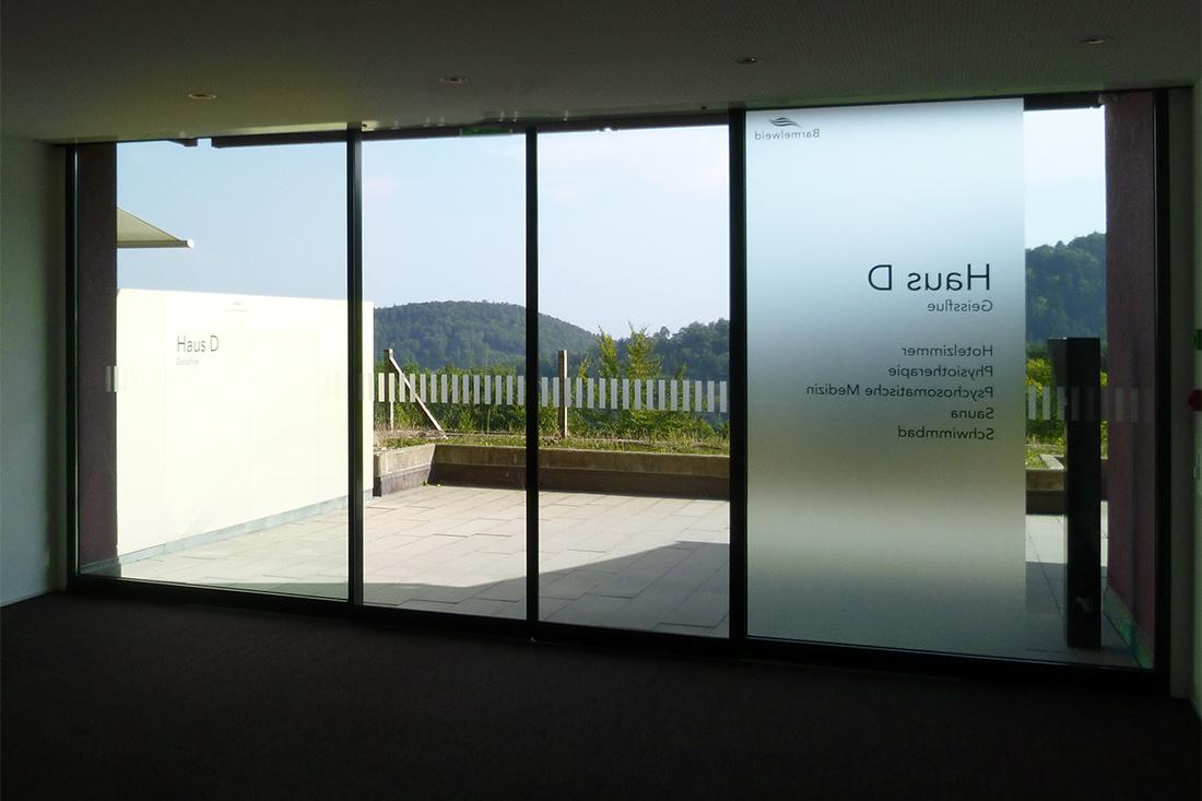 Wegleitung auf Glasfenster von innen: VTuerbeschriftung mit Sichtschutzstreifen. Auflaufschutz mit Milchglasfolie.