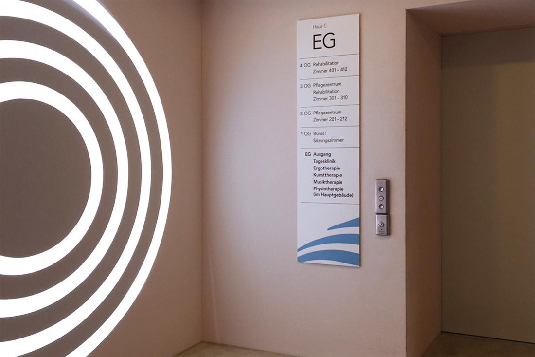 Liftschild und leuchtende Kreisform an der Wand