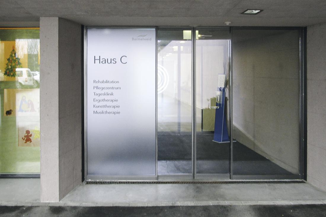 Vollflaechiger Sichtschutz kombiniert mit Folientext auf der Glas-Tuer beim Eingang zu Haus C