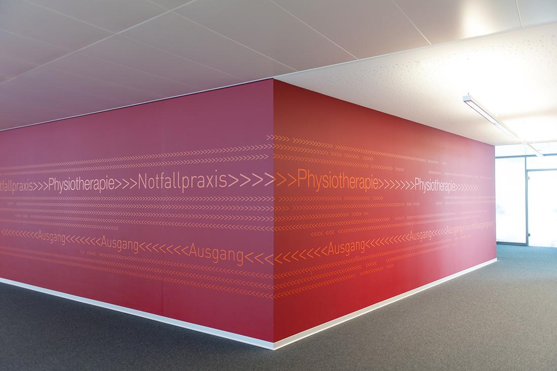 Wegweisung zur Notfallpraxis, Physiotherapie, Notausgaung auf Fototapete um die Ecke: Auffaellige, vollflaechige, rote Wandgestaltung mit orangen Leitpfeilen.