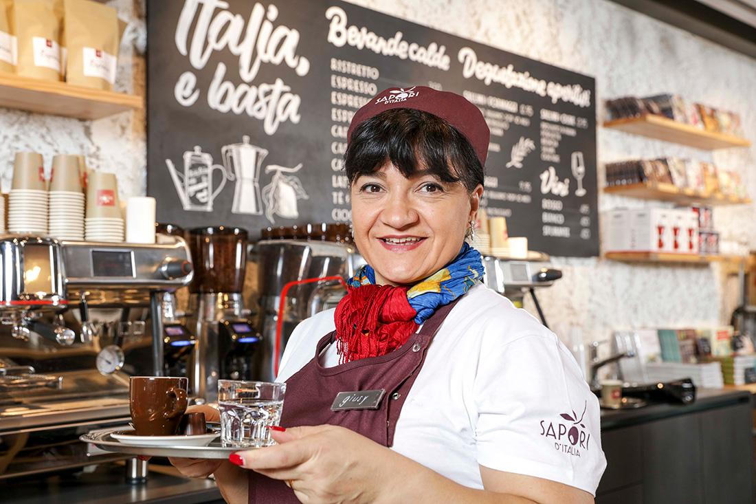 Kellnerin des Delikatessen-Ladens serviert Kaffee und laechelt in die Kamera; italienischer Charme und Temperament