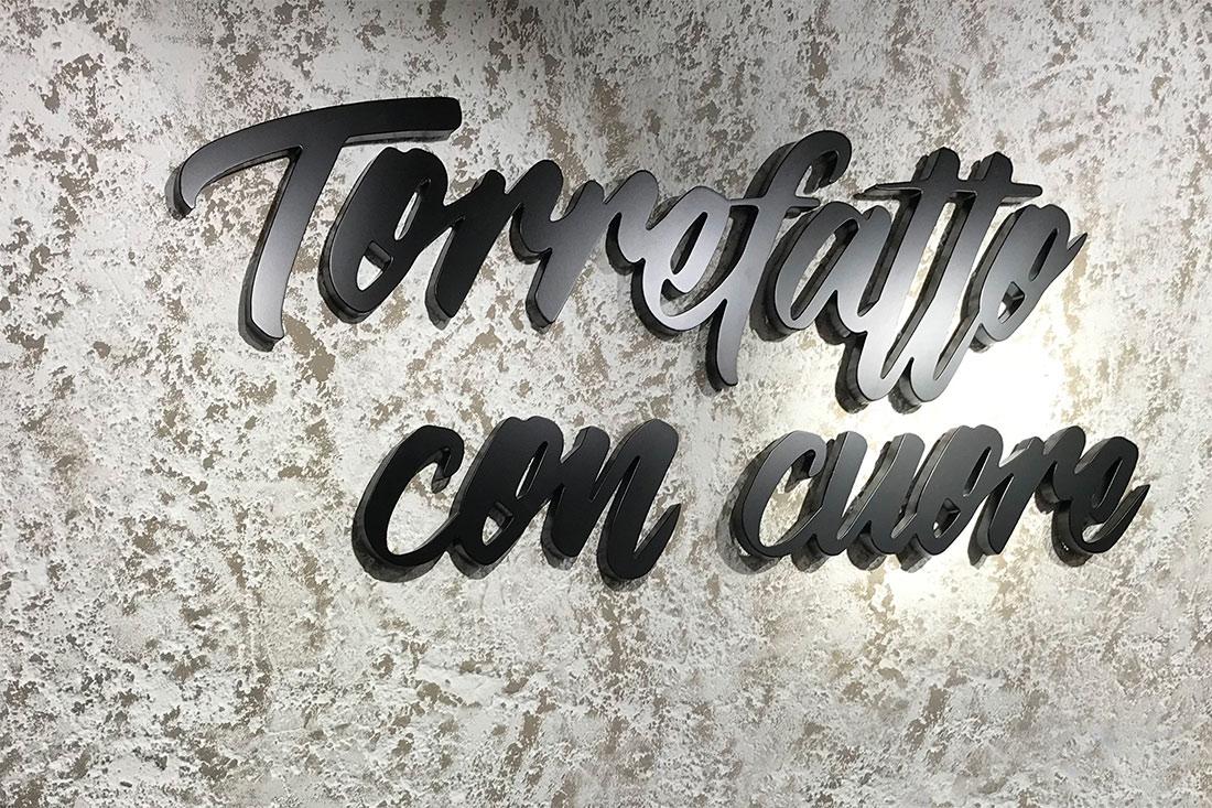 Werbetechnik im Ladenbau mit einem gefraesten schwarzen 3D-Schriftzug - Torrefatto con cuore - Kaffee mit Herz geroestet