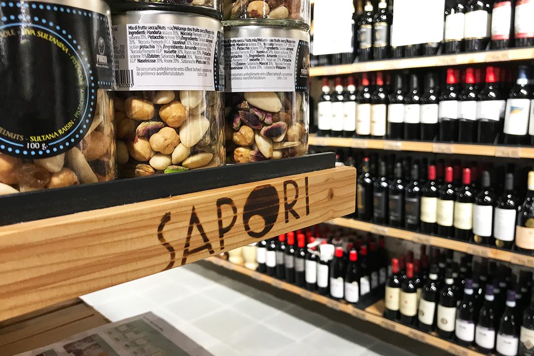 Das Logo Sapori als stylisches Brandzeichen an einem Holzregal