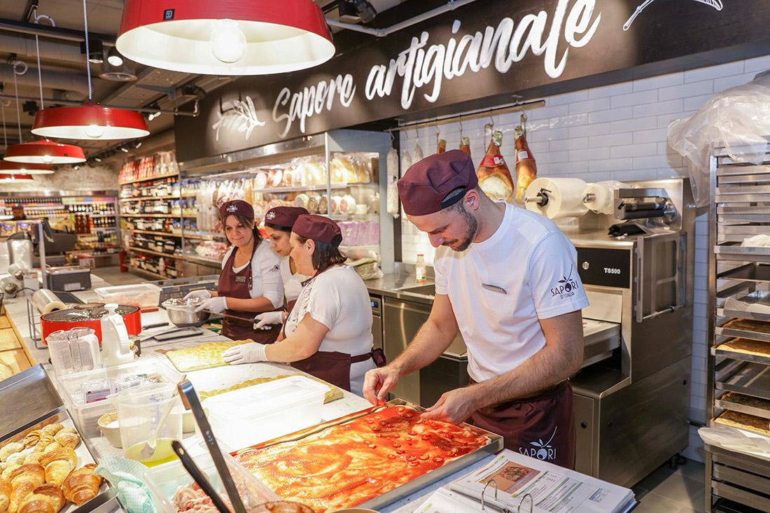 Pizzas werden handgemacht und an der offenen Theke belegt; ein Bild mit italienischem Duft