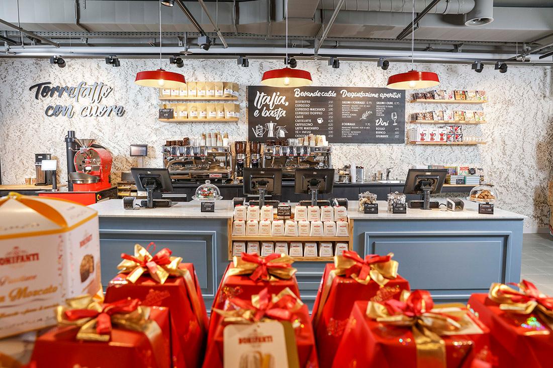 Werbetechnik Ladenbau: Verkaufstheke mit hellblauem Holz und hell marmorierter Rueckwand, rote Haengelampen und im Vordergrund rot-goldene Panetone-Verpackungen
