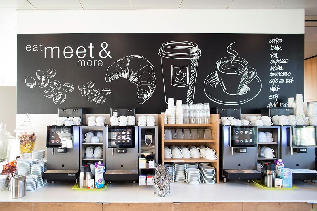 Wandtafel mit handgezeichneten Motiven als Rueckwand der Kaffemaschine
