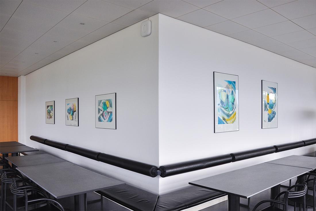 Vorher: Die weisse Wand mit Bildern im Essbereich und graue Tische
