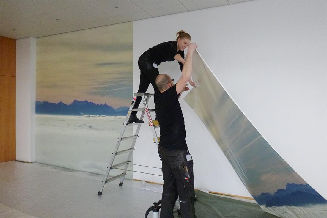 Zwei frontwork-Mitarbeiter bringen die grossflaechige Wandfolie mit Bergmotiv an