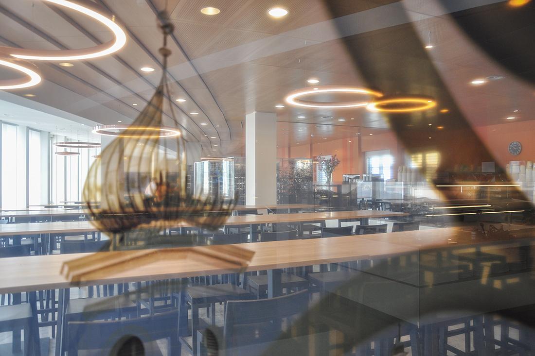 Spiegelung im Glaspanel des Restaurants: Lichtdurchfluteter Raum