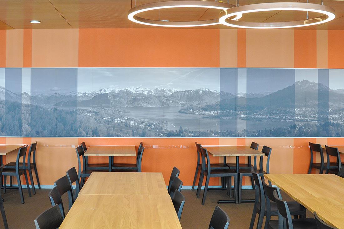 Wandfolierung mit Vierwaldstaettersee-Motiv sorgt fuer Tiefe, blauelich auf oranger Wand