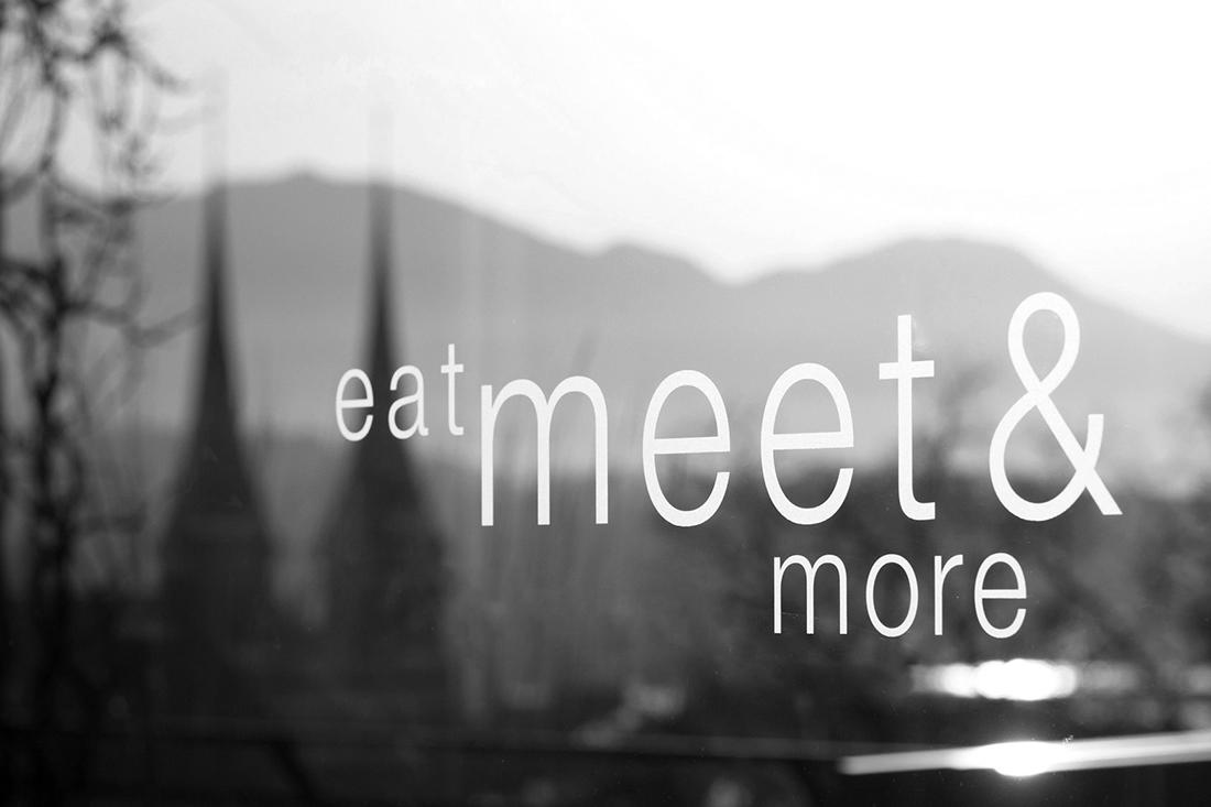 Wandfolie mit Schwarz-Weiss-Motiv als Hintergrund fuer den Slogan: eat meet and more