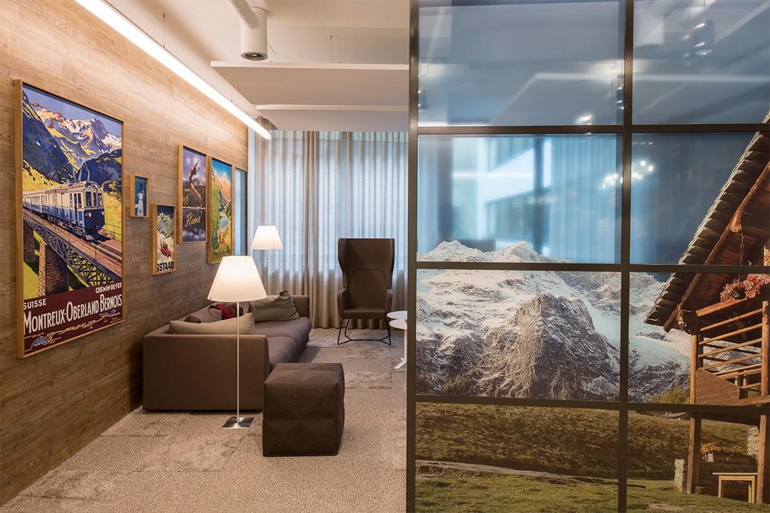Wandgestaltung fuer die Lounge, Raumtrenner: Glaswand mit Bergweltmotiv im Vordergrund, Blick in die Lounge mit Bilderwand