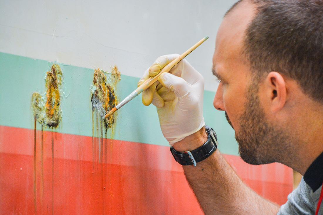 Spezialist beim Werk: Kuenstliche Verschmutzung durch Bemalen einer Betonmauer mit Dreck-Effekt