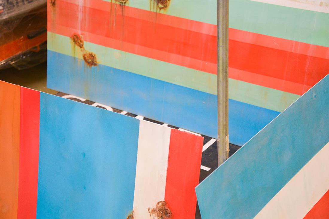 Blechwaende in Blau-Rot-Weiss mit Rostflecken in Vintage-Umsetzung