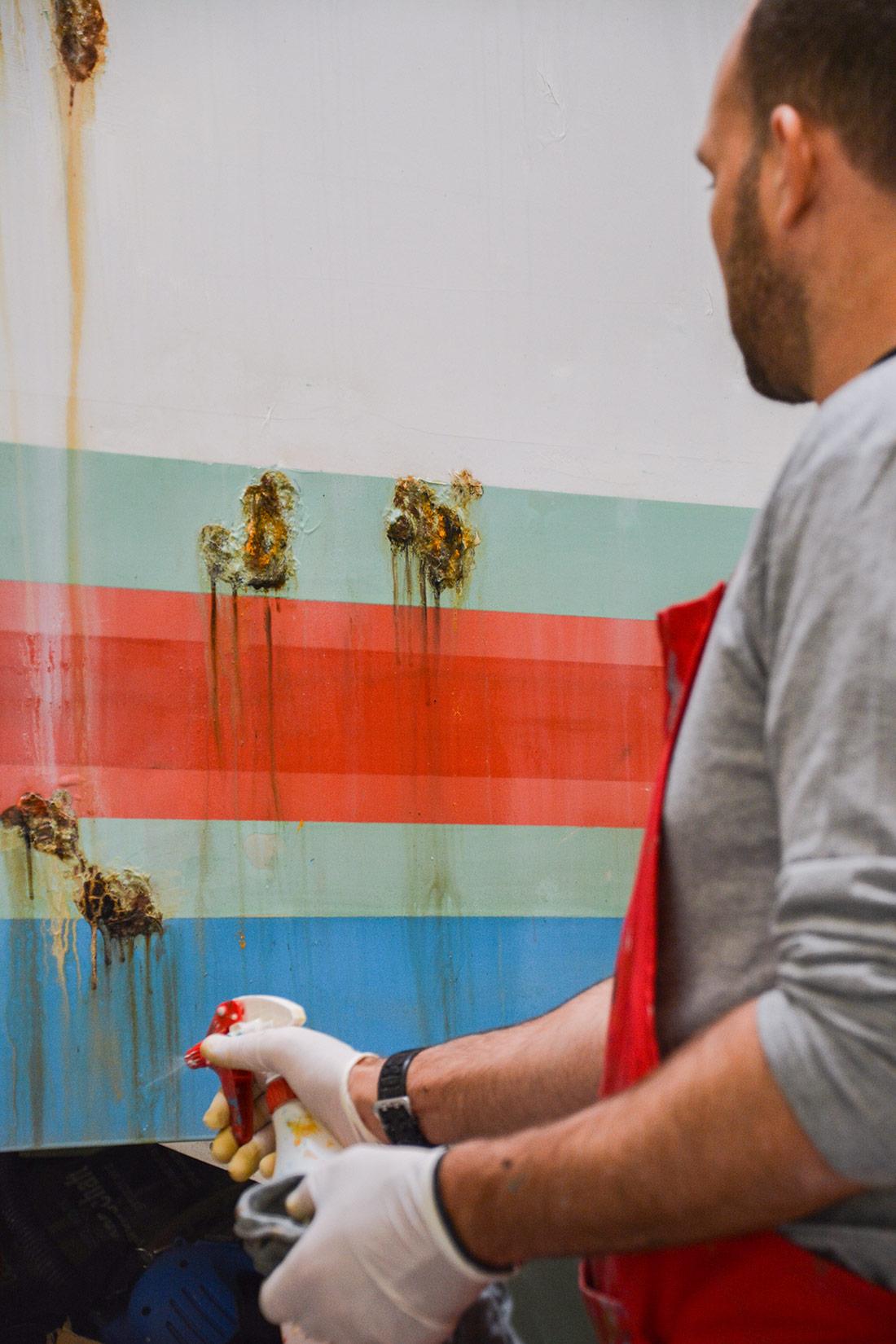 Betonwand wird mit Schmutz-Elementen besprueht: Dreck der an der Mauer herunterlaueft