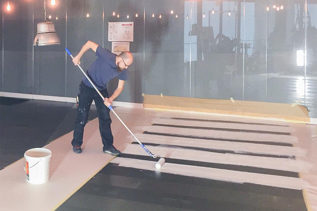 Frontwork-Mitarbeiter malt Fussgaenger-Streifen auf den Boden
