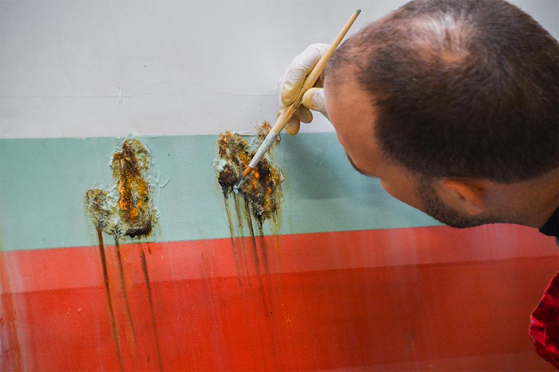 Frontwork-Mitarbeiter beim malen von Rostflecken auf Blech